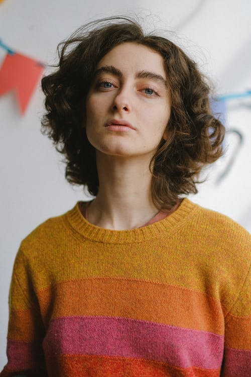 Low angle of young pensive curly haired female in colourful warm jumper looking at camera