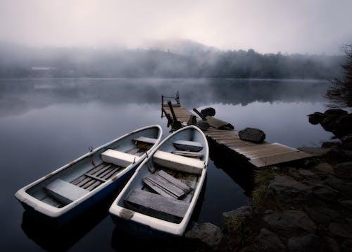 Boats near pier on lake in fog
