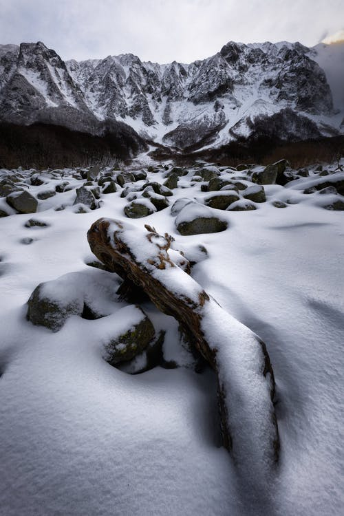 Picturesque view of mountain terrain with stones and log under snow in front of rocky hills