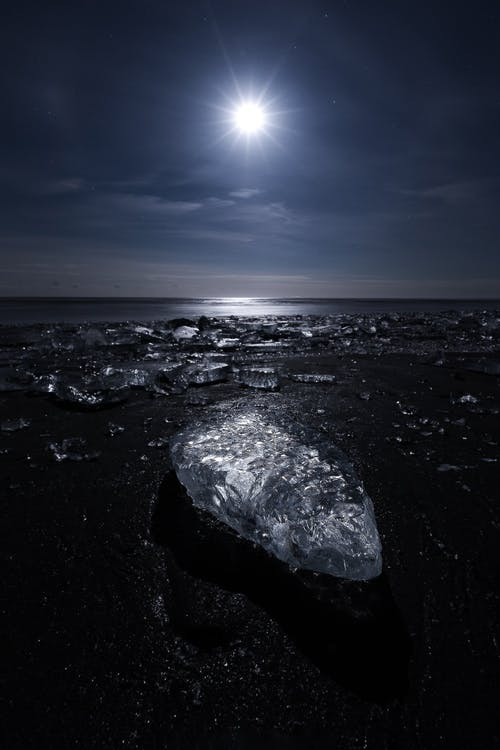 Rough stone surface with frozen ice near calm sea under clear sky with bright light