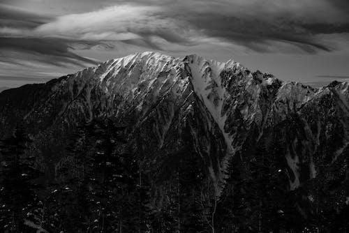 High snowy mountain ridge under clouds