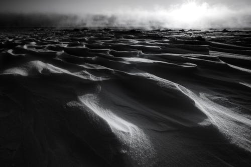 Black and white of summer desert terrain with sandy hills in foggy weather
