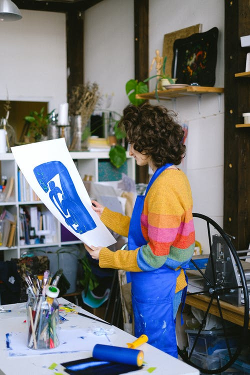 Curly woman with painting in studio