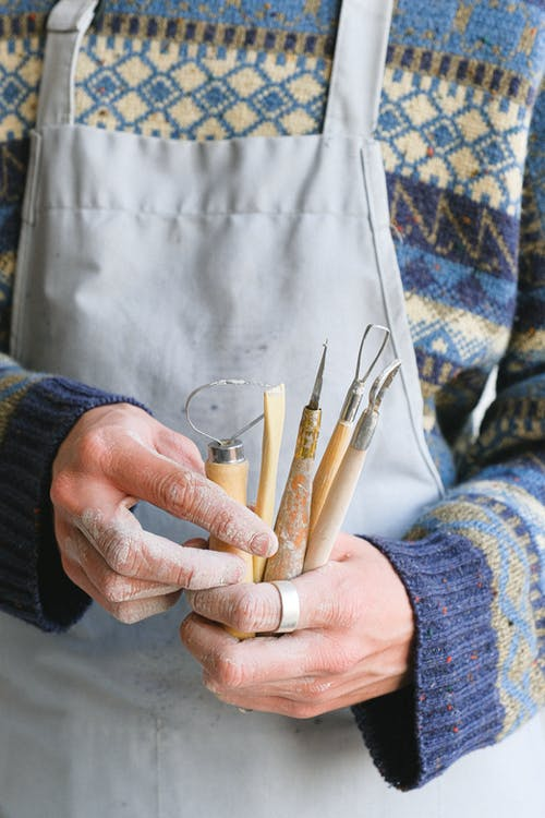 Unrecognizable male potter wearing apron standing with abundance of professional instruments with wooden handles for clay during work in studio
