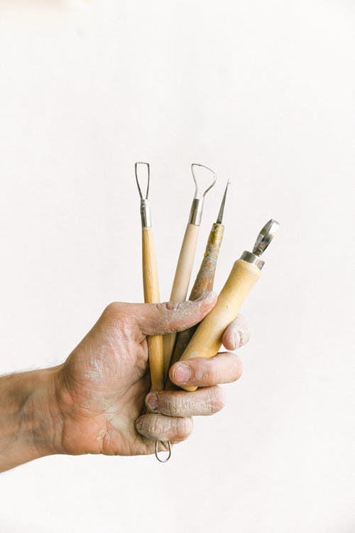 Anonymous male master with set of instrument for clay modeling in dirty hand standing on white background in professional workshop