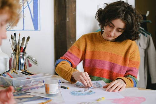 Focused woman drawing picture in studio