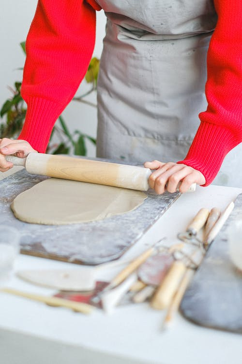 Unrecognizable female master standing at table with wooden rolling pin wearing apron rolling piece of clay while making pottery in professional workshop