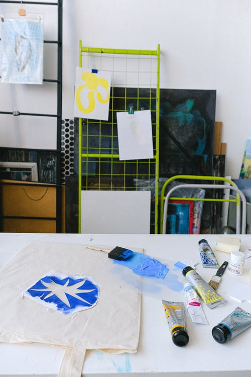 Bag with blue print placed on white table with paintbrush and set of tubes for painting in creative workshop with paintings