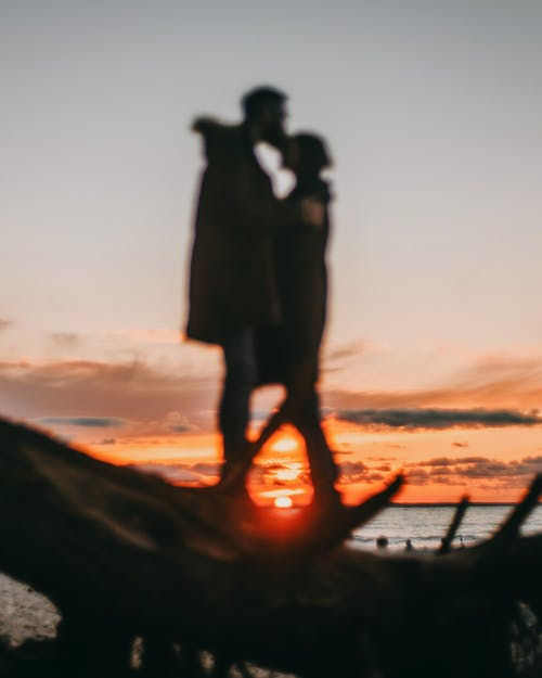 Defocused man cuddling and kissing unrecognizable woman in casual clothing while standing on coast of ocean against vibrant sky covered with orange clouds