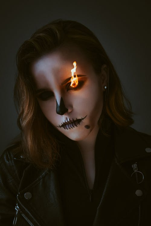 Woman in Black Leather Jacket With Lighted Candle