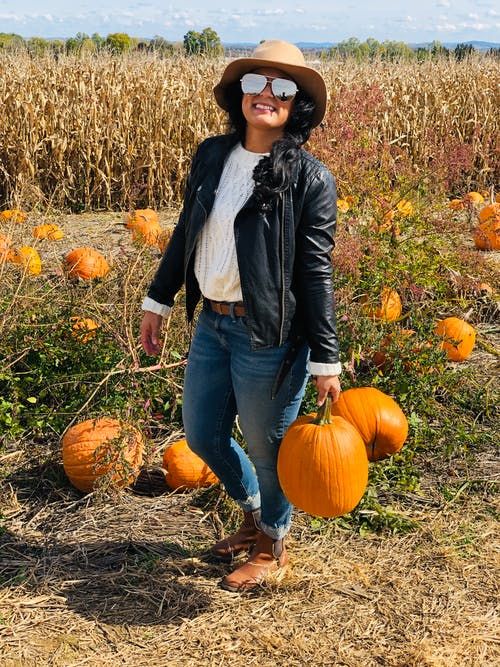 Woman in Black Leather Jacket and Blue Denim Jeans Holding Two Pumpkins
