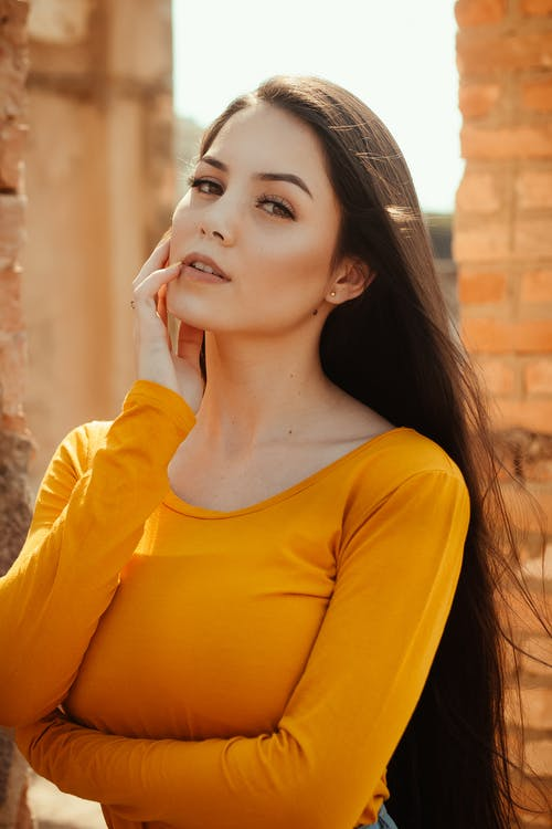 Stylish woman with long hair in bright yellow sweatshirt