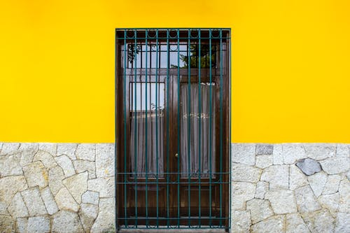 Exterior of wall with stony foundation and yellow wall with wooden door with metal gate in street in daytime outside