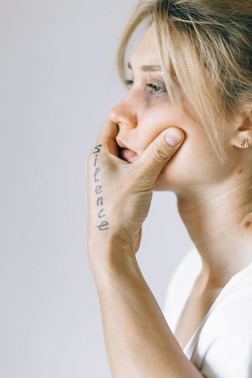 Woman in White Shirt Covering Her Face With Her Hand