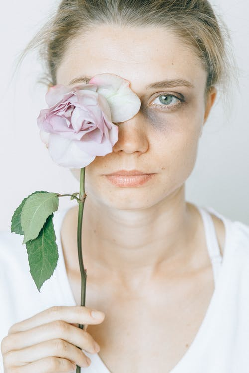 Woman in White Scoop Neck Shirt Holding White Rose