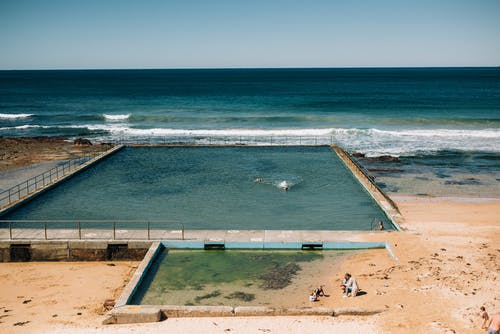 Sandy seashore with swimming pool near waving water with foam under clear blue sky