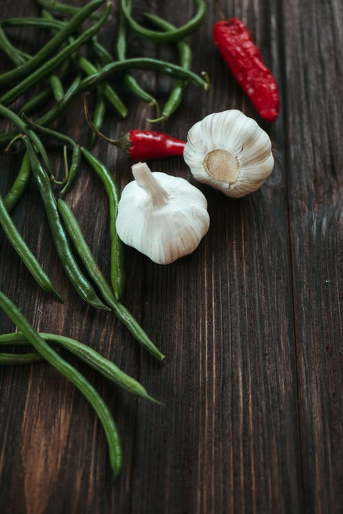 White Garlic and Red Chili on Brown Wooden Table