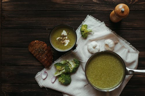Top view of saucepan with broccoli puree soup on white napkin with garlic and toasted bread slice