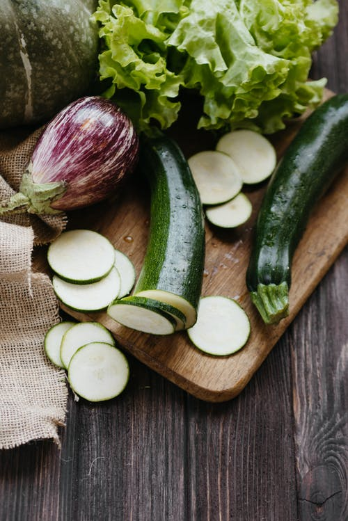 Sliced White Onions and Green Vegetable on Brown Wooden Chopping Board