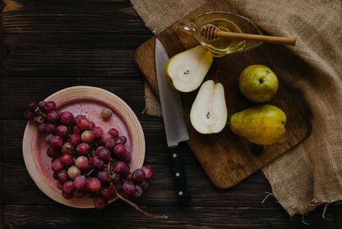 Board with pears and honey near grapes
