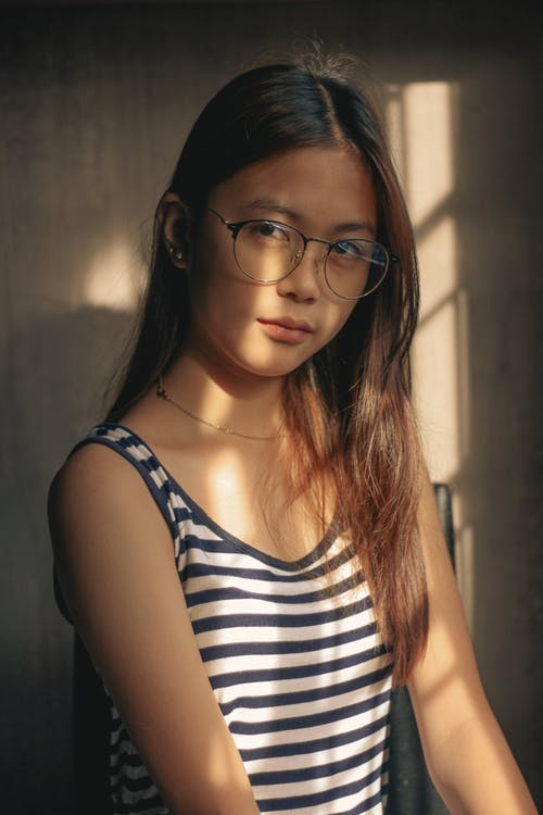 Asian teenage girl with long hair in stripped undershirt and eyewear in lights of sun