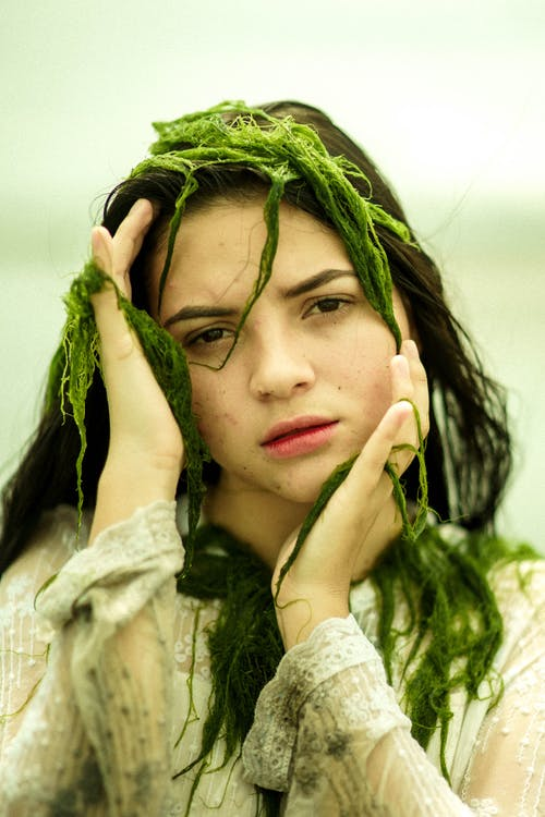 Sad young ethnic female in wet dirty clothing with see weed on face and hands at cheeks looking at camera in daytime on blurred background
