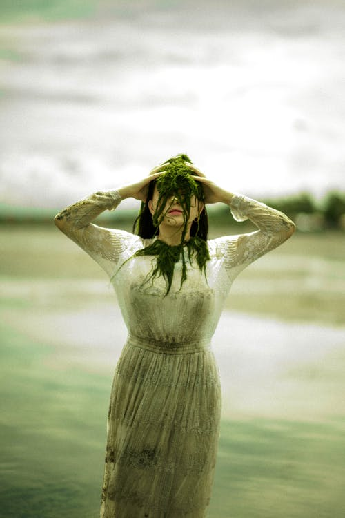Faceless woman with see weed on face by pond in daytime
