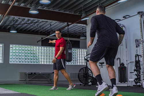 Strong man training with instructor in gym