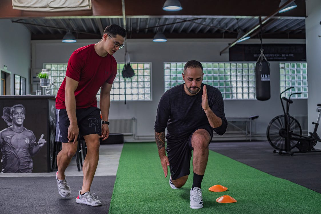 Full body of focused man in sportswear doing stretching exercises with coach in contemporary fitness center