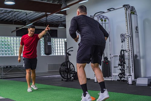 Back view of muscular man in sportswear doing exercises with trainer in modern fitness club