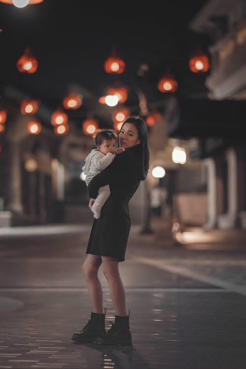 Side view full length positive young Asian female in black dress holding adorable child on hands while standing on empty street at night