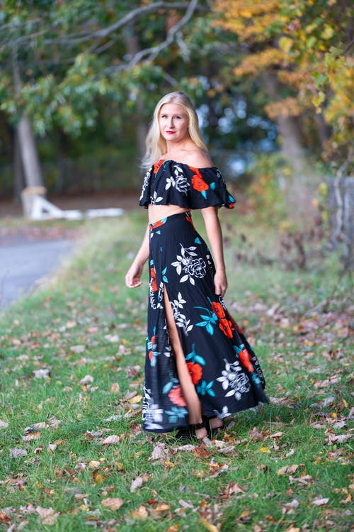 Full length of pensive female with long hair wearing maxi dress and standing on blurred background of park