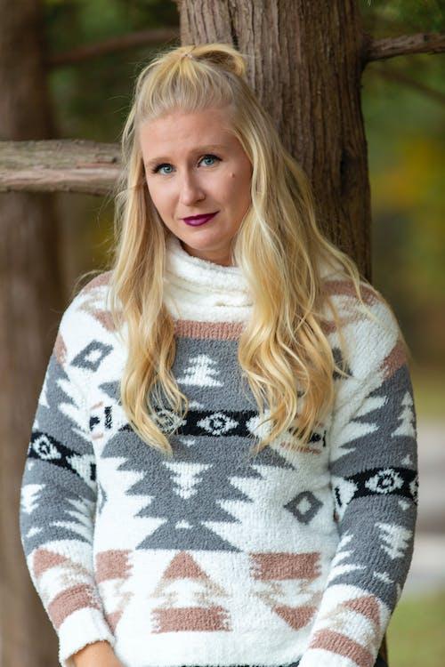 Wistful woman in casual sweater near tree