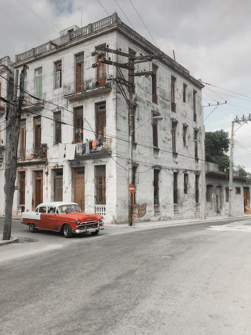 Abandoned building near asphalt road with car