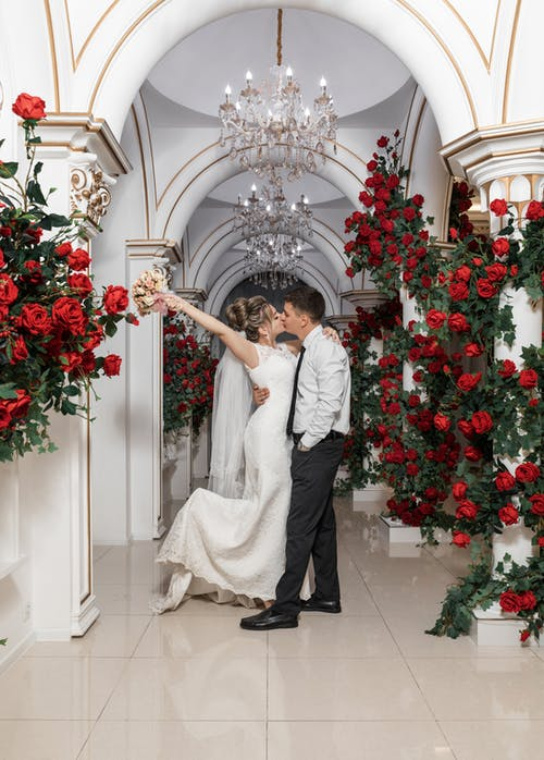 Full body of elegant bride and groom kissing in luxurious hallway with red roses celebrating wedding