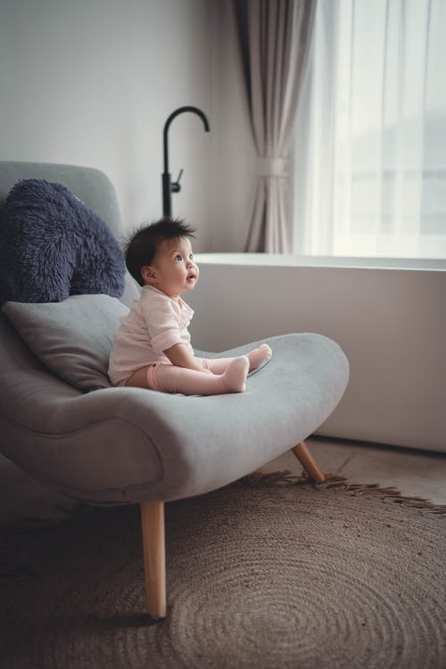 Curious Asian kid resting on comfortable chair
