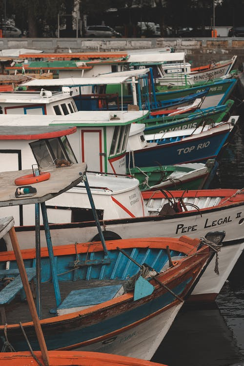 Colourful old small fishing boats moored on river pier in city in daytime