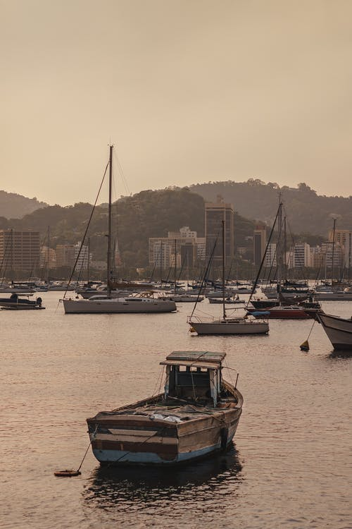 Fishing boats and sail boats on calm river in front of big city with modern buildings and mountains in evening