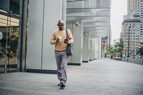 Full length of serious African American man having coffee to go while texting on smartphone walking down street in center