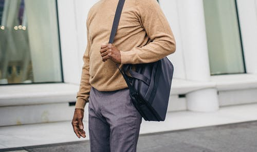Faceless African American elegant male in jersey and pants carrying case bag on street