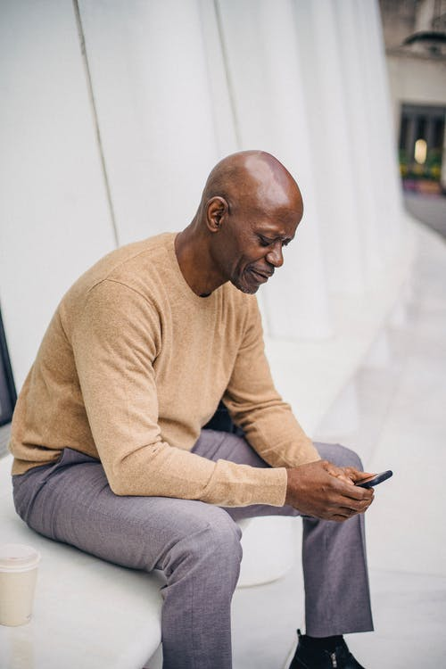 Elegant bald African American entrepreneur browsing mobile phone while resting on street bench with cup of coffee