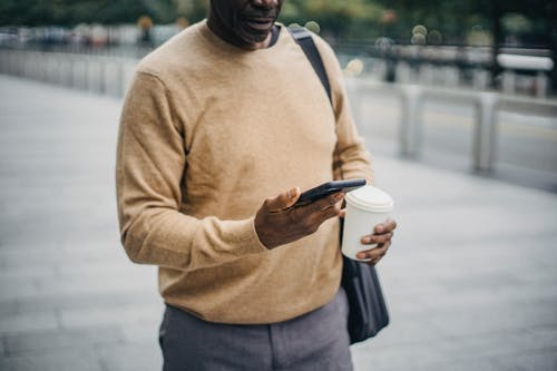 Crop businessman texting on phone walking down street