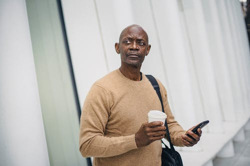 Mature bald black man with smartphone and coffee cup standing on street looking around in downtown