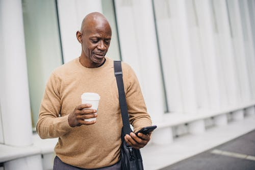 Content ethnic businessman texting on phone in city