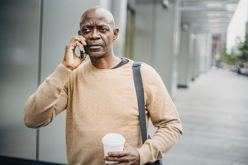 Focused African American male with coffee cup chatting on mobile phone walking down street