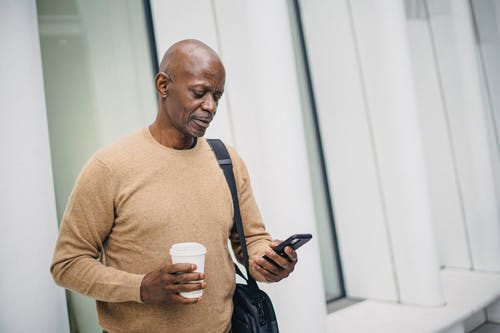 Serious black man with smartphone and takeaway coffee