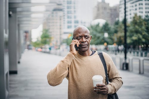 Focused adult African American businessman with coffee cup walking in downtown and talking on phone