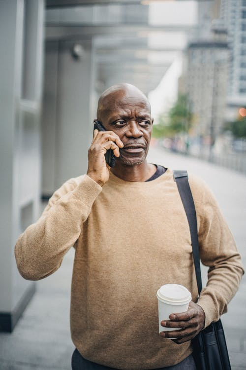 Mature businessman with coffee speaking on phone in downtown