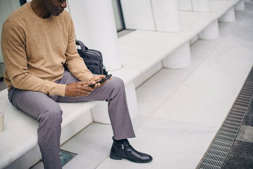 Crop businessman texting on phone resting on street bench