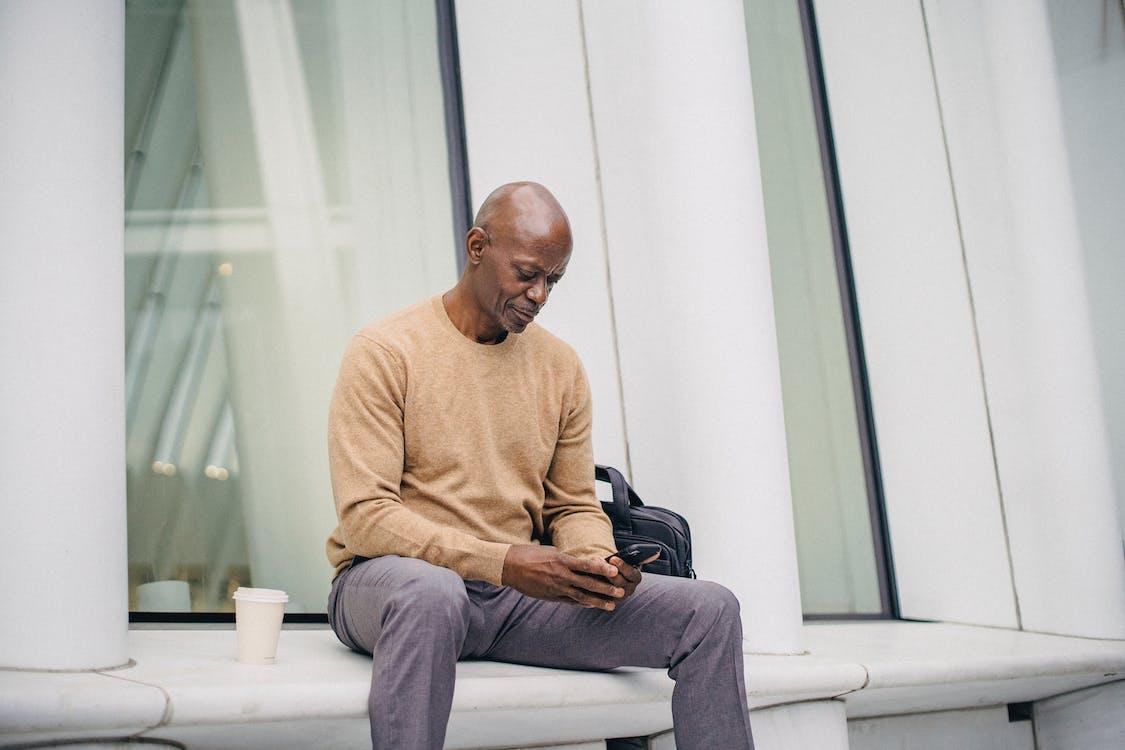Focused black man using mobile phone on bench